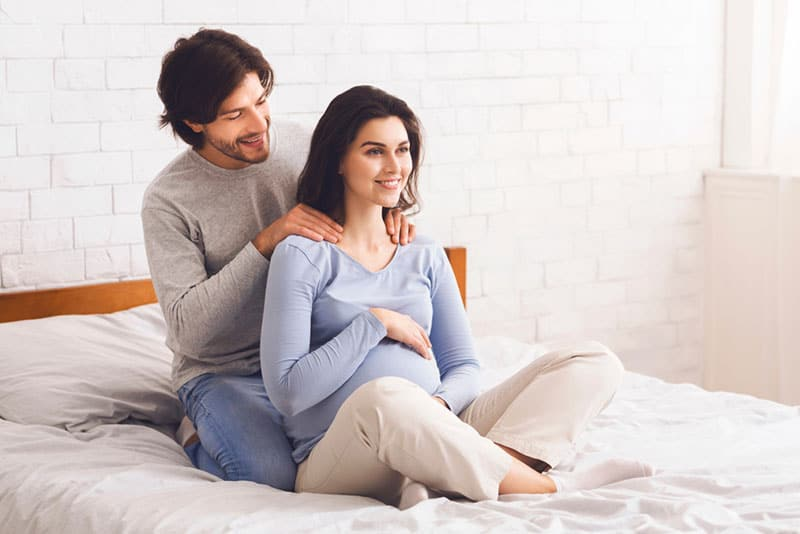 husband giving massage to pregnant wife on the bed