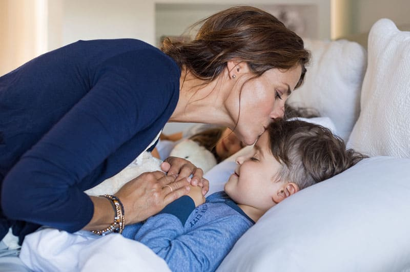 mother kissing her son in forehead for a good night