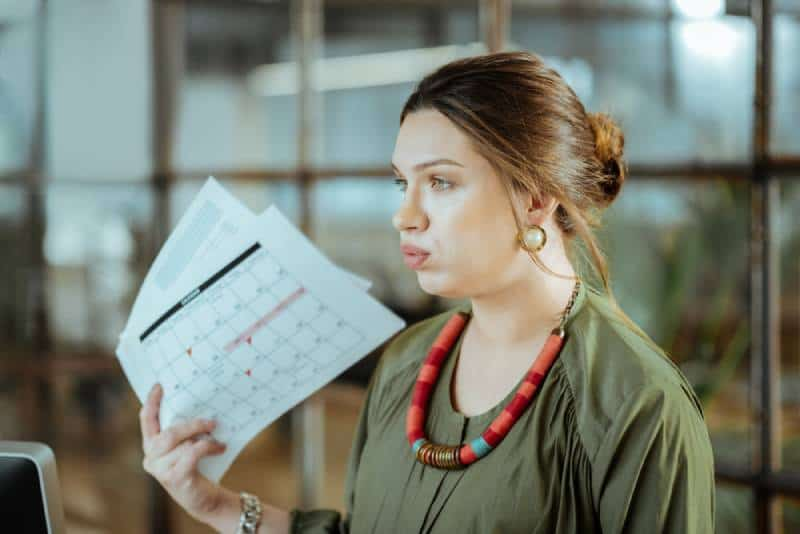 ark-haired pregnant woman feeling short of air after working in office