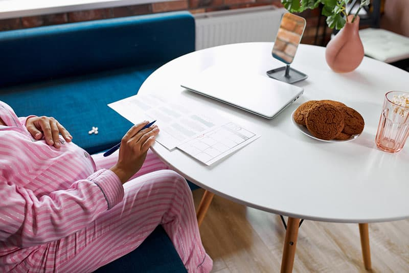 pregnant woman sitting by the table and writing on paper