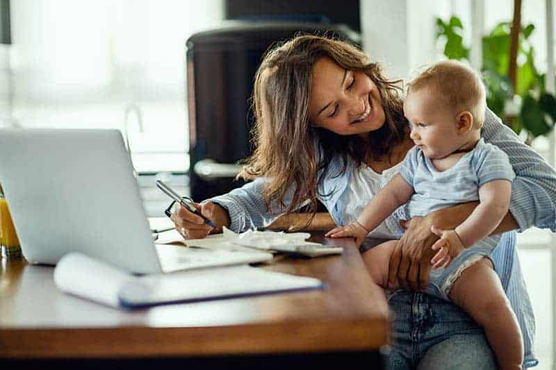 smiling mom with baby writing a note