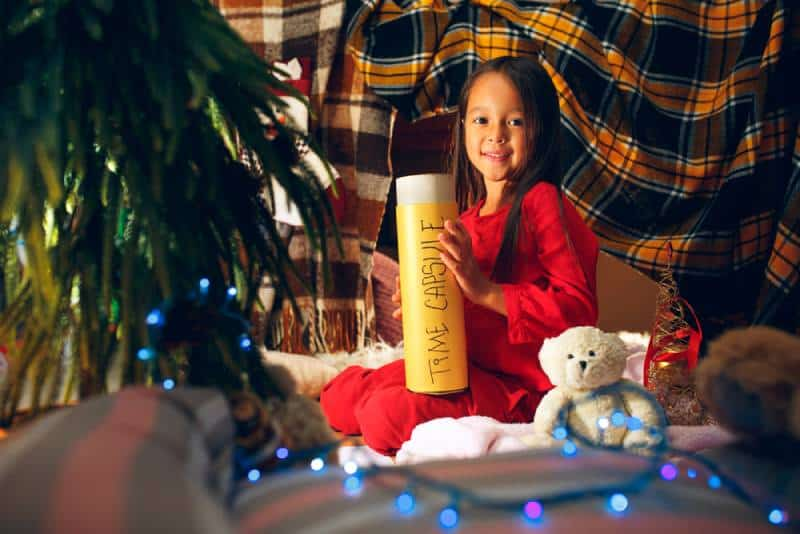 Cute little child girl sits near Christmas tree and holding a time capsule