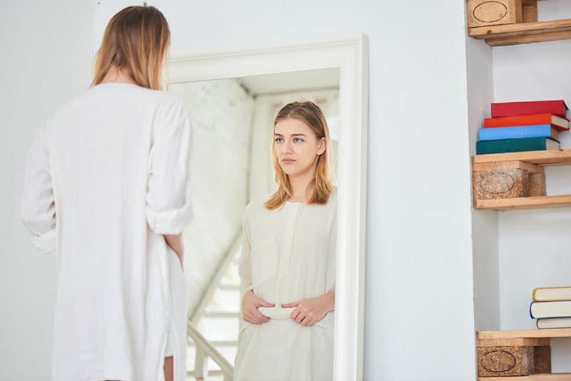 worried woman looking at mirror