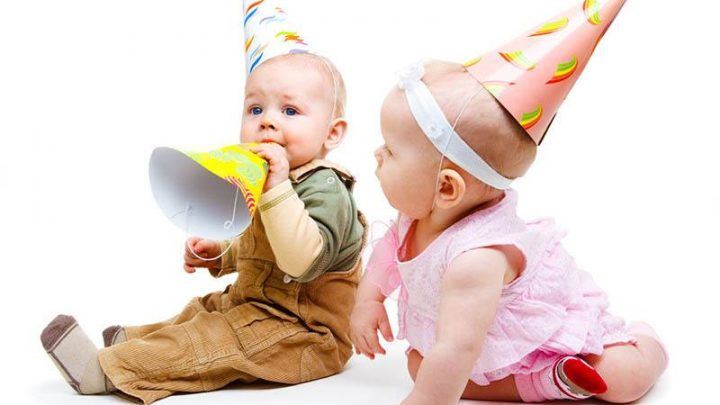 Baby boy and baby girl playing with birthday hats