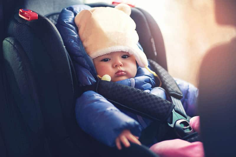 adorable baby girl in winter clothes sitting in the car seat