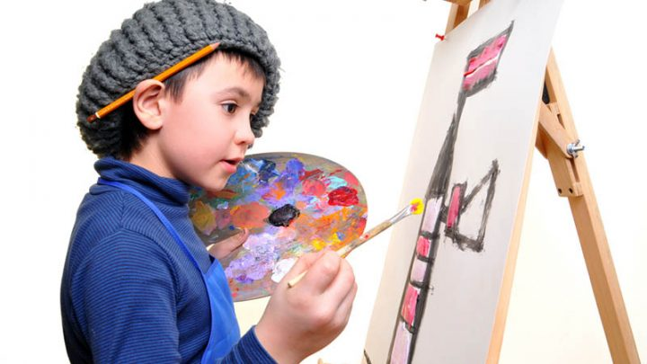 cute little boy painting on easel