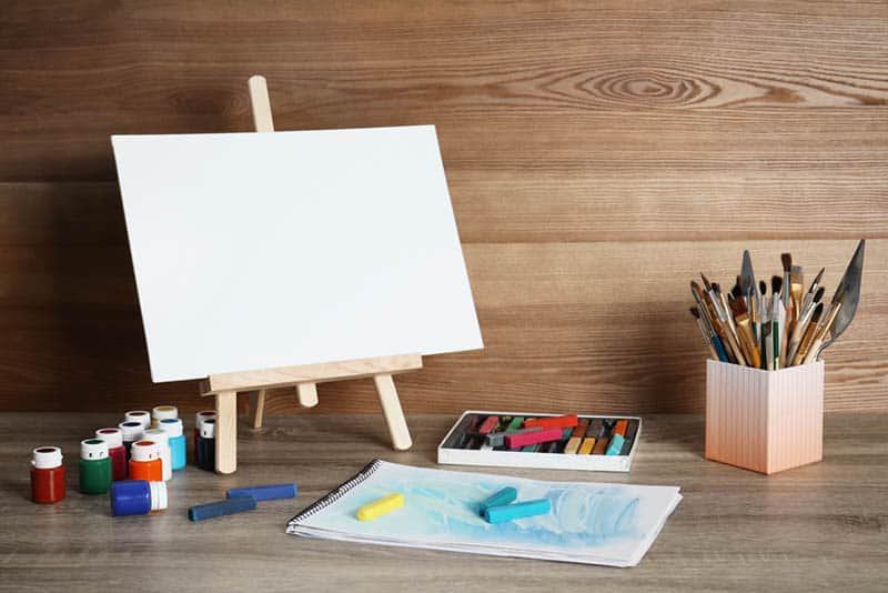 art easel with brushes and colors on the table
