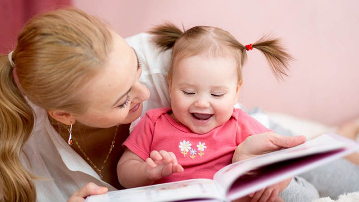 mother and baby holding a book