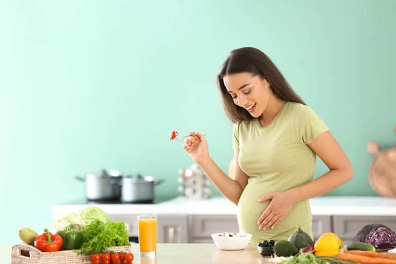 beautiful pregnant woman eating healthy food in the kitchen