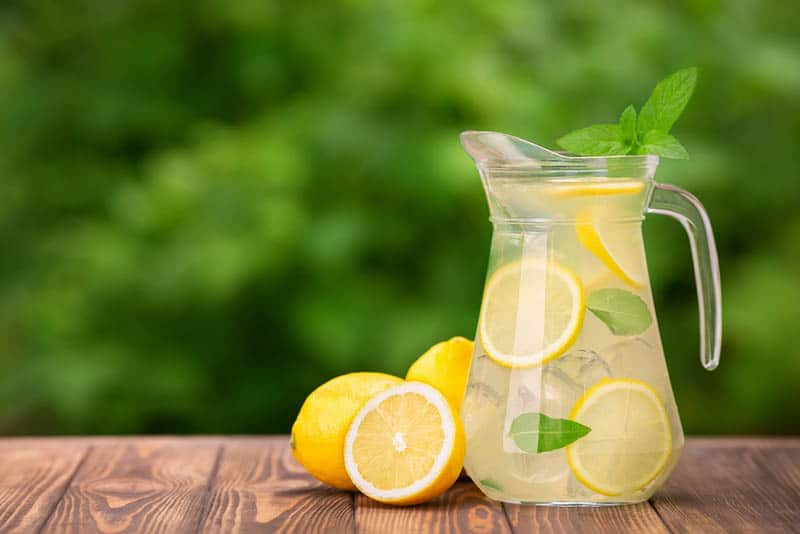 bottle full of lemonade with pieces of lemon