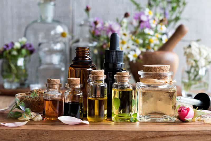 bottles of essential oils on the table with herb and flowers in background