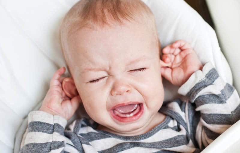 cute baby boy crying in the cribe