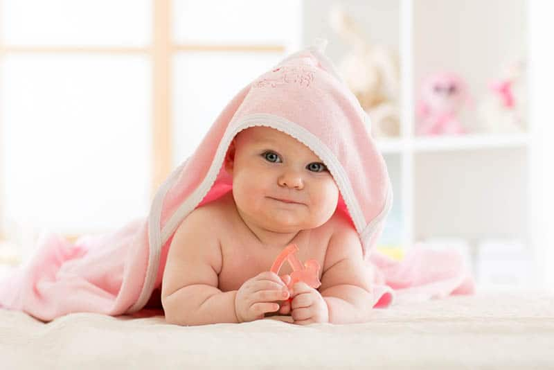 cute baby covered with pink towel after bath