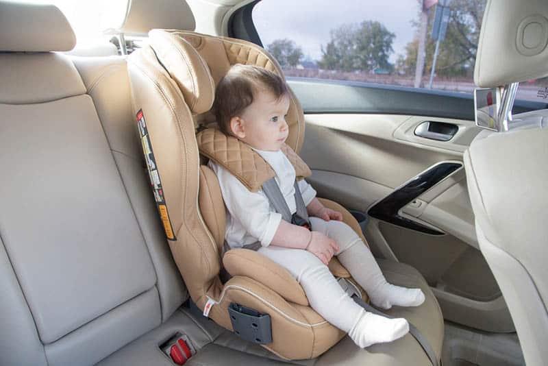 cute baby girl sitting in a car seat