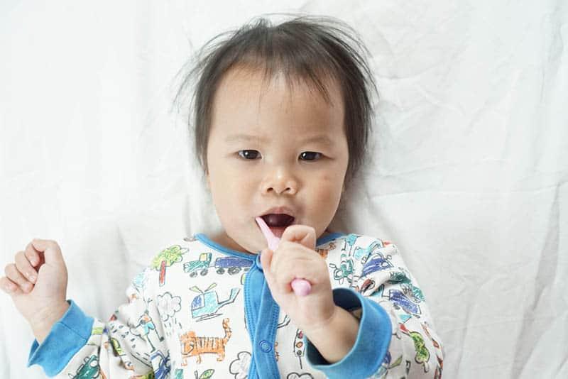 cute baby using brush for teeth massage