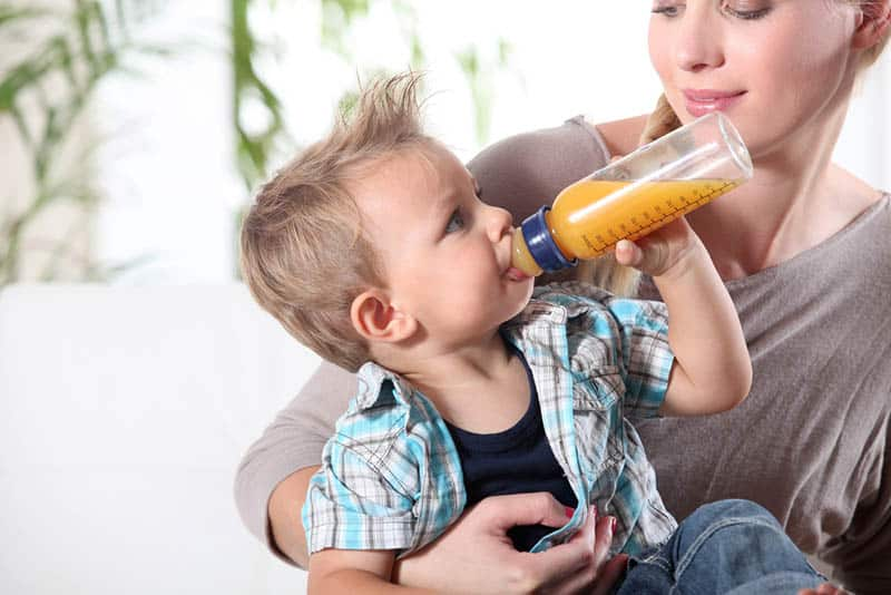 cute boy drinking juice from bottle and sitting on mother
