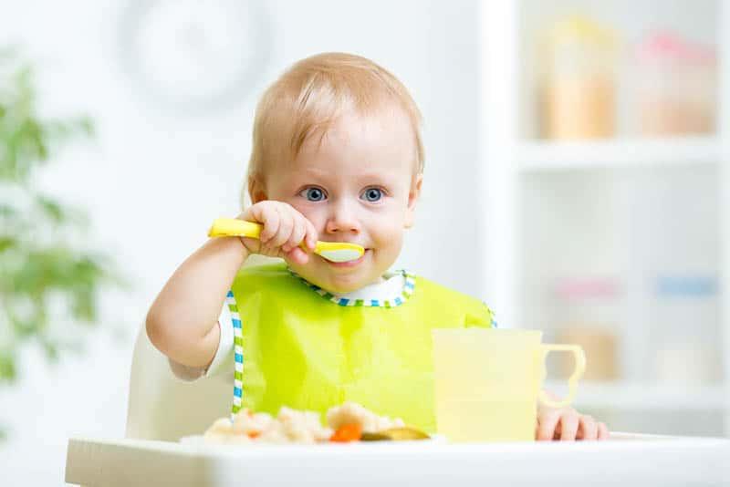 cute kid eating healthy food with spoon