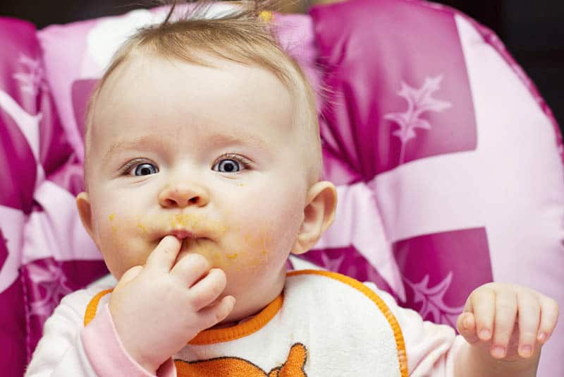 cute little baby with blue eyes eating