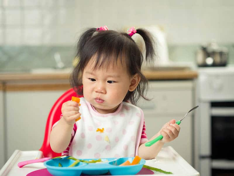 cute little girl eating vegetables in the high chair