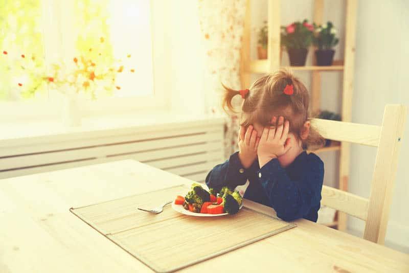 cute little girl refusing to eat vegetables