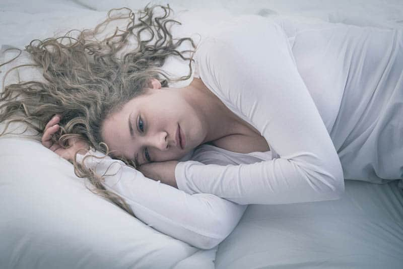 depressed woman lying on bed