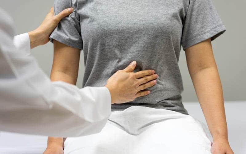 doctor examining woman abdominal wall