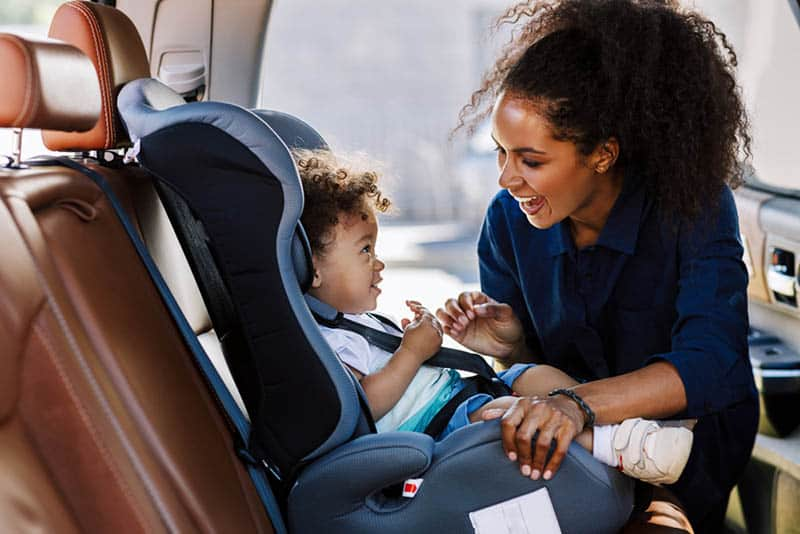 happy young mother smiling with baby in the car seat