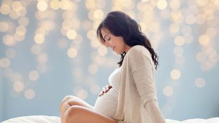 pregnant woman sitting on bed