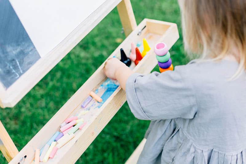 little girl playing with colorful crayings outdoor