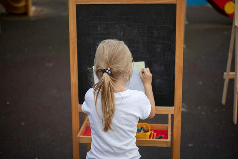 little girl sitting and trying to paint on the easel