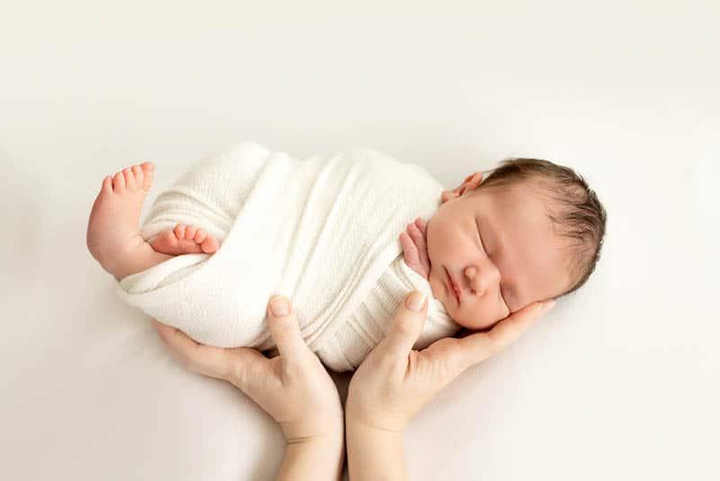 newborn baby sleeping in hands