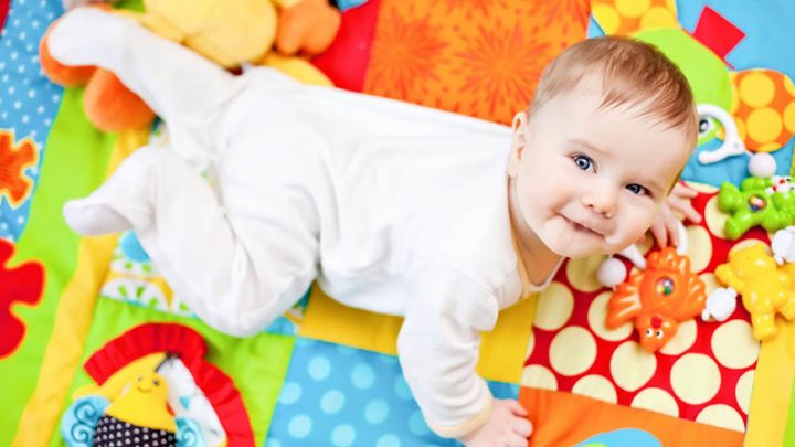 baby playing on colorful playing mat