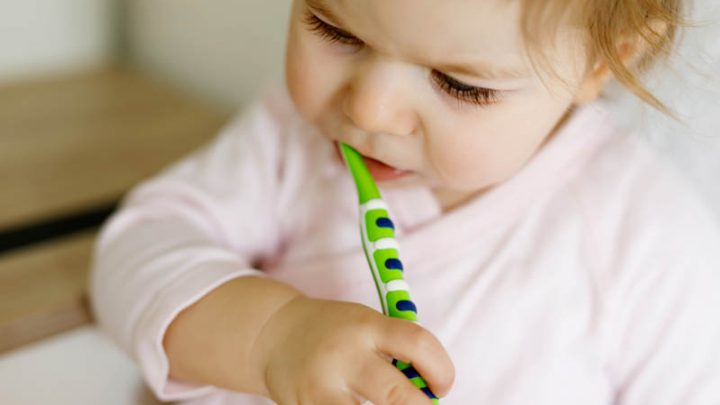 baby brushing teeths with colored brush