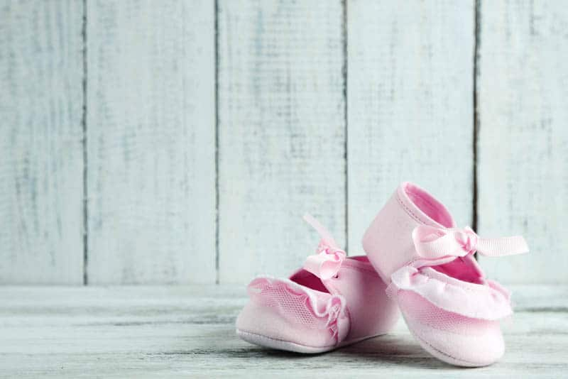 pink toddlers shoes on wooden background