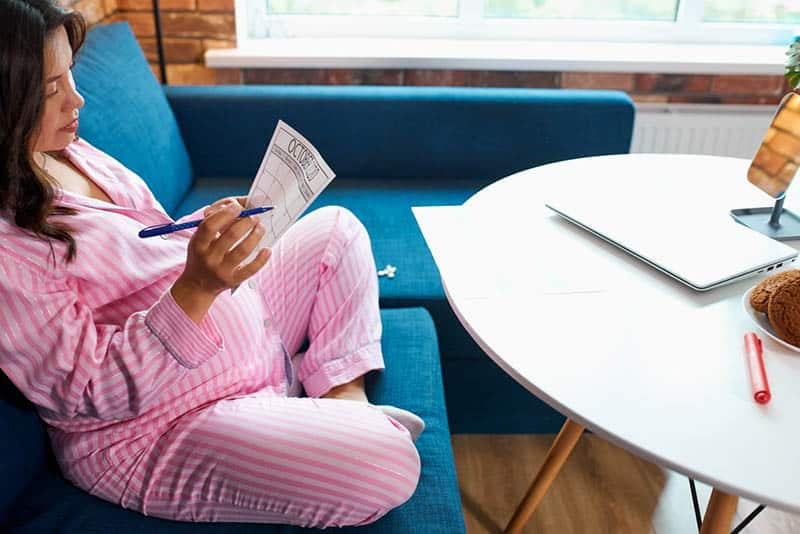 pregnant woman sitting at home and reading a birth plan