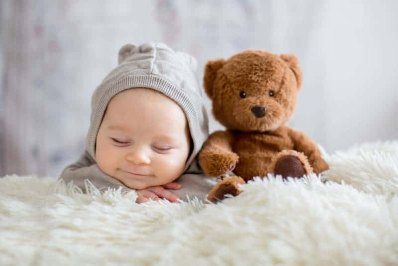 smiling baby boy sleeping with teddy bear