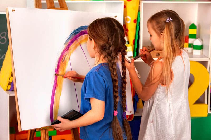 two cute little girls painting on easel