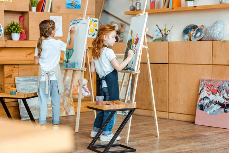 two little girls painting with colors in the room