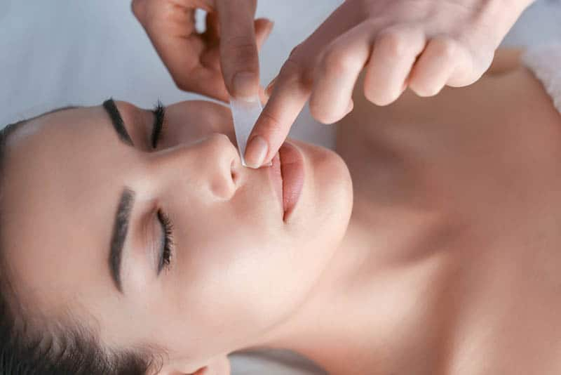 woman doing face depilation in beauty salon