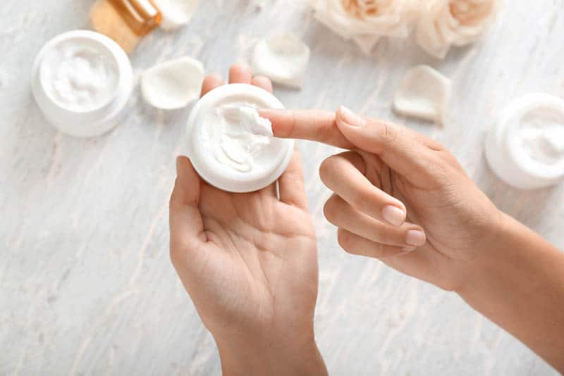 woman holding cream for face