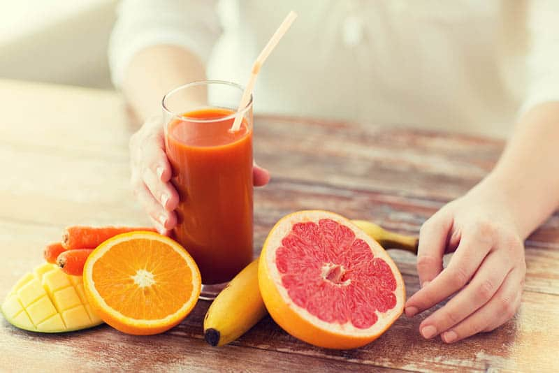 woman holding fresh orange juice with fruits on the table