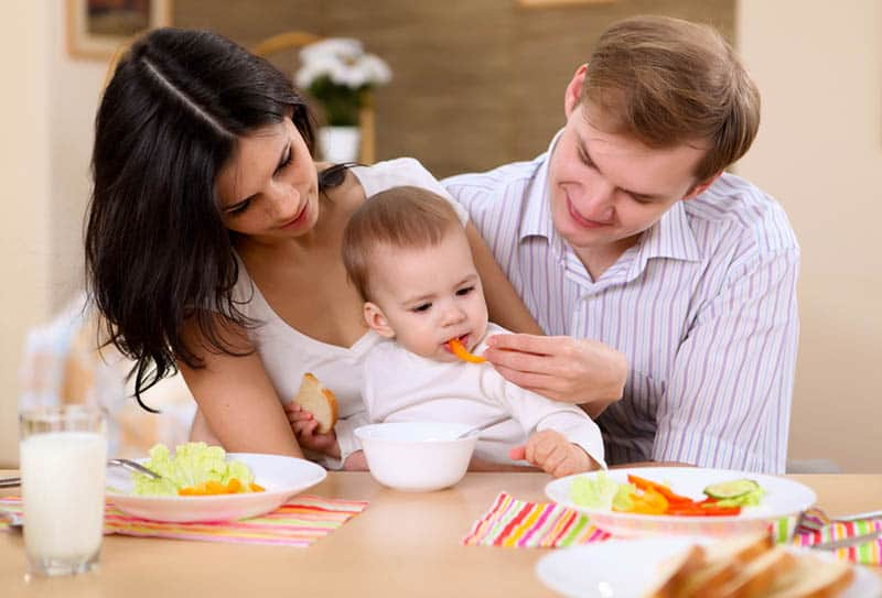 young parents feeding their child with vegetables