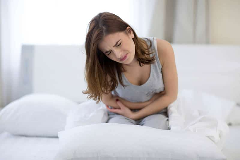 young woman feeling big pain in stomach