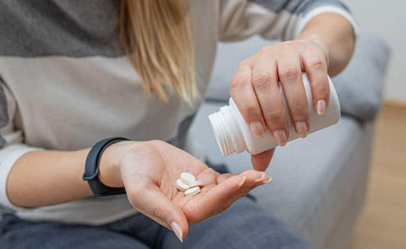 young woman holding a plastic bottle with pills