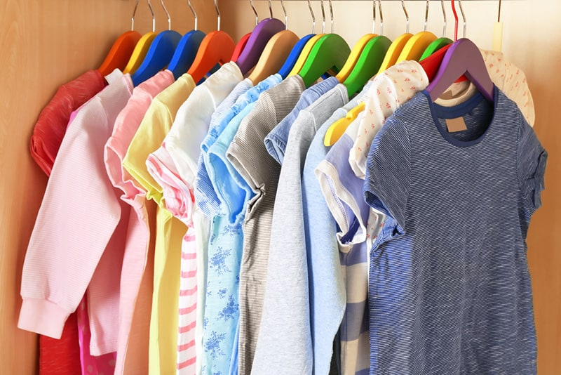 Kid's colorful clothes on hangers in the wardrobe