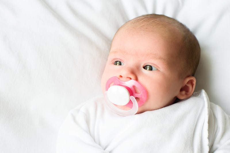 adorable baby lying on white sheets and sucking pacifier