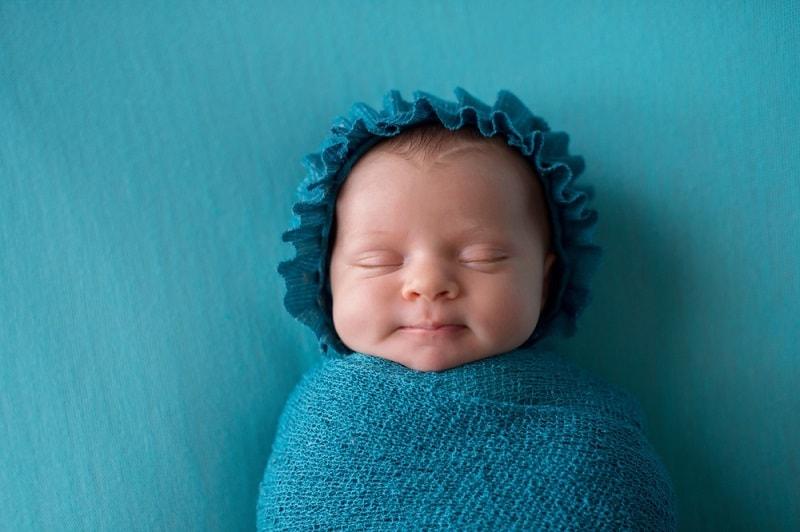 newborn baby boy sleeping wrapped in a blue swaddle