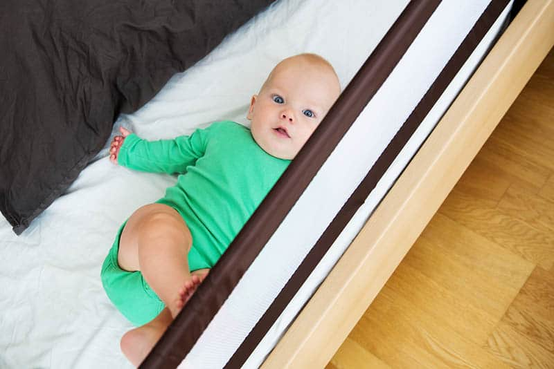baby lying in bed protected with guard rails