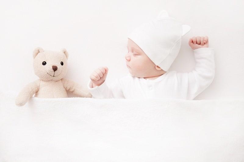baby sleeping next to a white teddy bear