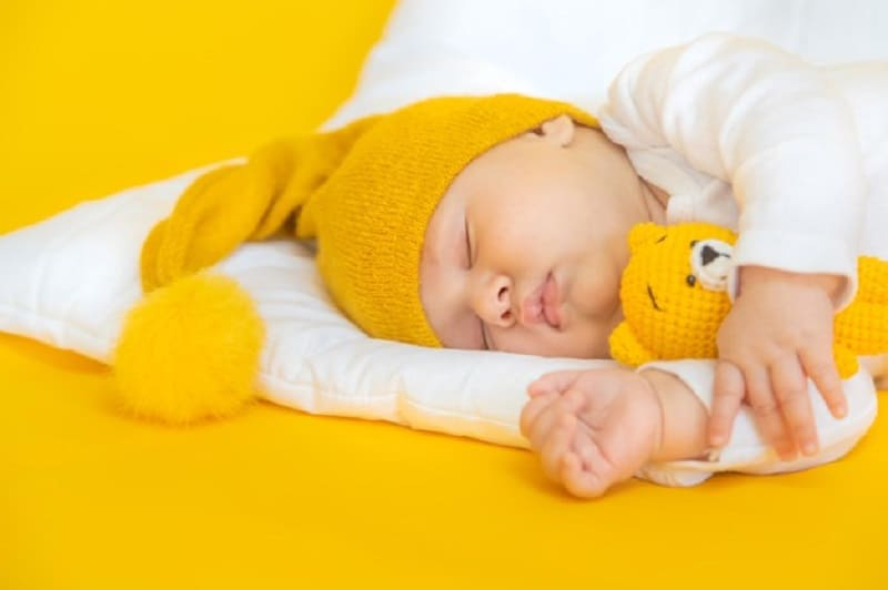 baby sleeping with a yellow hat and teddy bear